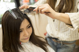 Fototapety Young women are dyed the color of the hair in a beauty salon