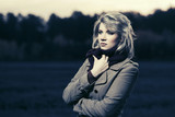 Sad young blond fashion woman in classic coat walking outdoor