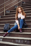 Young fashion woman in grey coat with handbag sitting on steps