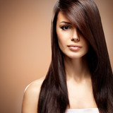 Fototapety Beautiful young woman with long straight brown hair.