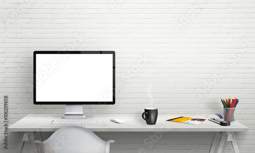 Isolated computer display for mockup in office interior. Work desk with keyboard, mouse, cup of coffee, paper, pencils. Free space on wall for text.