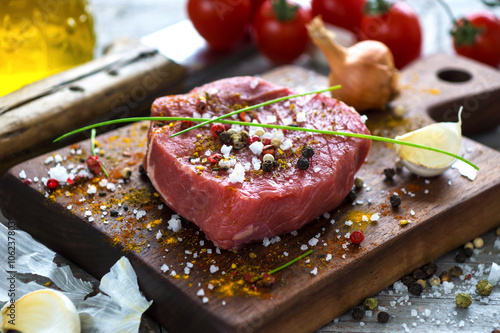Poster Fresh raw beef steak on wooden background