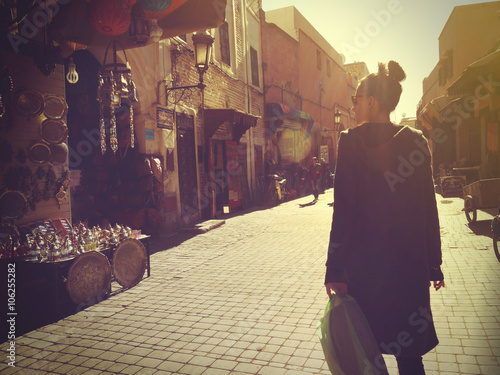Poster Marokko Young woman shopping in the Marrakech Medina at sunset