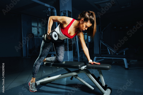 Póster Young woman at the gym back workout with dumbbells