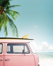 Vintage auto geparkeerd op het tropische strand (zee) met een surfplank op het dak