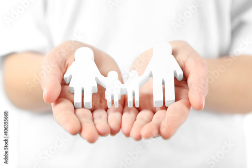 Fototapeta samoprzylepna Female hands holding family figure, close up