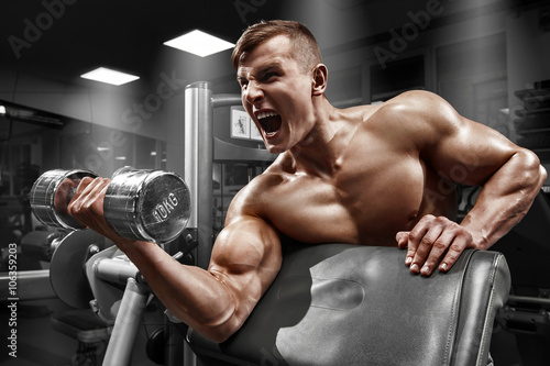 obraz lub plakat Muscular man working out in gym doing exercises with dumbbell at biceps, strong male naked torso abs