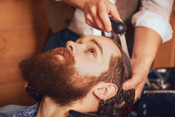 Barber washing head of bearded man