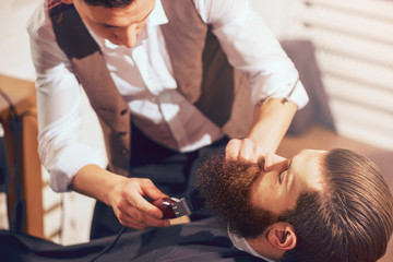 Professional barber cutting beard of pleasant man