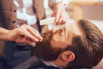 Professional barber cutting beard of handsome man