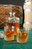 Two glasses and a decanter of whiskey on a green table top, against a background of old barrels