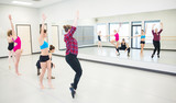 group of young dancers practicing in front of mirror