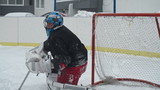 Ice hockey goaltender falling while catching a puck and making a save in slow motion