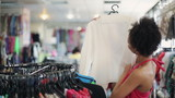 Sale, consumerism: Attractive african american woman chooses clothes in shop
