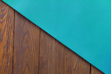 Detail of perforated blue yoga mats on the wooden background. Texture yoga mats and boards. Boards brown. The diagonal orientation. The concept of a healthy lifestyle. Weight loss and fitness.