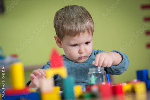 Kid is plaing with toys in nursery
