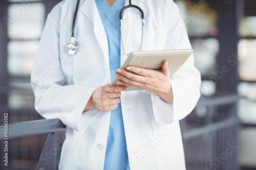 Midsection of doctor holding digital tablet Plakat