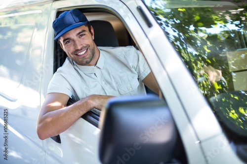 Cheerful delivery person sitting in van