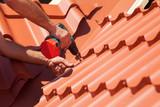 Worker on a roof with electric drill installing red metal tile on wooden house - 106705806