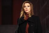 Fashion blond woman in black coat walking on night city street