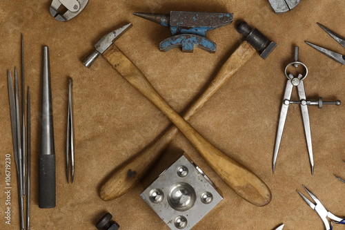 obraz lub plakat Tools of jewellery. Jewelry workplace on leather background. Hammers, anvil. Top view.