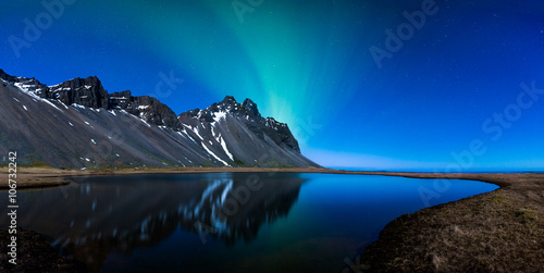 Fotobehang Antarctica Panoramic of Northern lights and mountains behind a lake