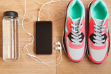 red and grey sneakers with grey shoelaces and bottle with water, mobile phone with white headphones on wooden background indoors