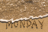 Week series - MONDAY - written on a sandy beach with the soft wave at sunny day.