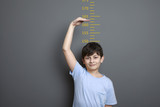 Cute boy is showing height on a wall scale. A cute boy is holding his arm up and showing his height on a wall scale.