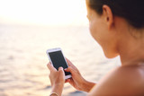Fototapety Smartphone woman texting on social media app looking at display screen for sms reading on ocean background on a sea cruise balcony or beach at sunset on holiday. Unrecognizable girl using smart phone.