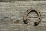 Rusty horseshoes on a wooden background - rustic scene in a country style. Old iron Horseshoe - good luck symbol and mascot of well-being in a village house in Western culture.