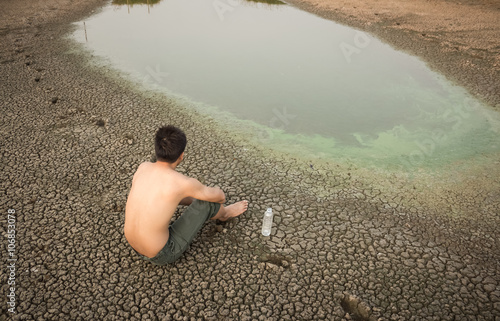 Water crisis, man sit on cracked earth near drying water.