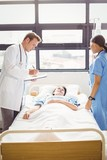 Doctor and a nurse examine a patient