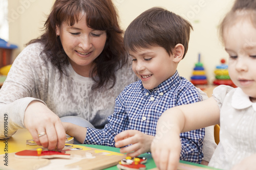 Fototapeta beautiful caucasian teacher collects the puzzle with a pupil