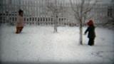 1960: Kids leaving fresh tracks in winter snow in white fenced backyard.