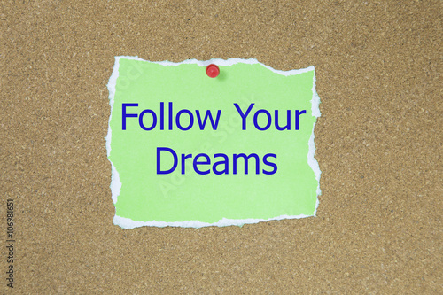 Poster The phrase follow your dreams in text on a green sticky note posted to a cork notice board