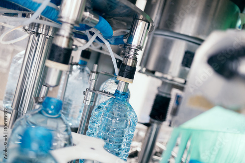 Robotic factory line for processing and bottling of pure spring water into canisters and bottles. Selective focus. © tamara83