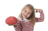 Fototapety young beautiful girl 6 to 8 years old playing with rubber brain having fun learning science concept