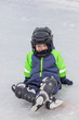 Little boy in skates sitting on ice
