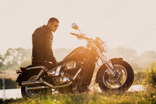 Poster young brutal man in a black jacket and glasses standing near a motorcycle
