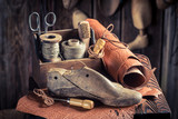 Small shoemaker workshop with shoes, laces and tools - 107082016