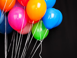 Fototapety Group of colorful balloons on ribbons over black