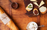 Savory and sweet snacks with French baguette on a wooden table, top view