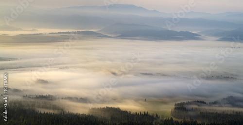 Dolina górska spowita poranną mgłą - 107111683