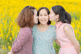 Young asian girls kissing their mother outdoor