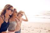 Happy young women walking on a beach