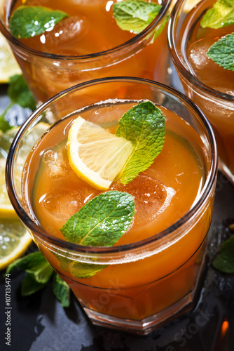 iced tea with mint and lemon in glasses on dark background