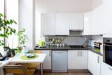 cucina bianca con accessori illuminata da luce naturale in appartamento dai toni chiari e freschi