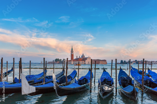 Gondolas moored by Saint Mark square with San Giorgio di Maggiore church in the
