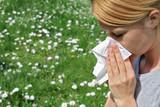 Pollen allergy, Springtime. Woman sneezing in a tissue